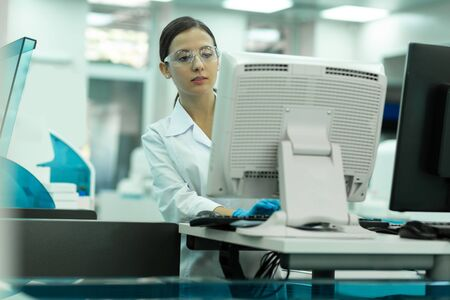 Lets work. Serious brunette woman wearing protective glasses while concentrating on task 写真素材