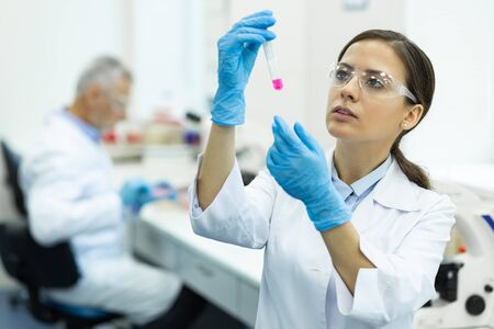 Blood analysis. Concentrated female person raising hand while looking at test tube