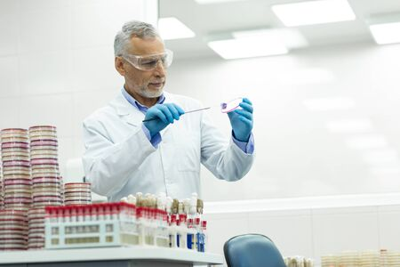 Modern laboratory. Concentrated bearded male person using sterile equipment while doing chemical research 写真素材 - 129802160