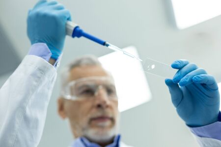 Chemical expertise. Attentive mature scientist wrinkling his forehead while looking at test tube 写真素材