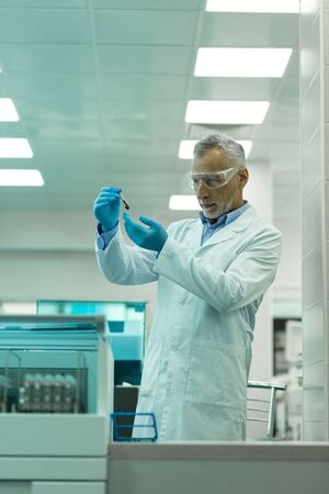 Lab coat. Concentrated scientist wearing protective glasses while working in laboratory