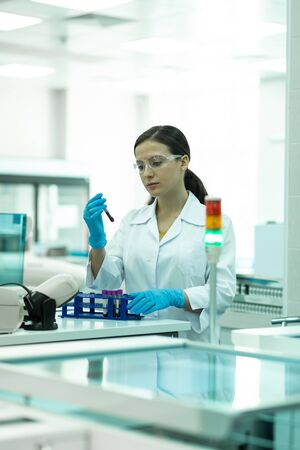 Deep in thoughts. Attractive brunette female person wearing lab coat while working in laboratory 写真素材