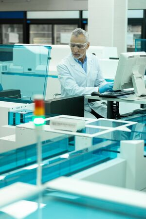 Lab worker. Serious medical worker wearing protective glasses while doing scientific research