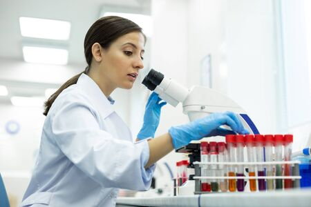 Be careful. Delighted brunette girl wearing uniform while working in laboratory 写真素材