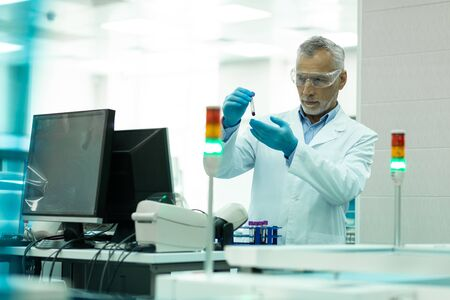 Reagents examination. Serious grey-haired researcher being in lab coat while examining reagent
