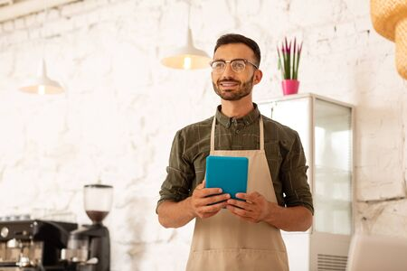 Holding tablet. Owner of coffee shop holding little blue tablet while ordering foods