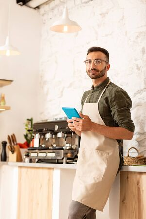 Working all day. Businessman owning coffee shop wearing apron while working all day long