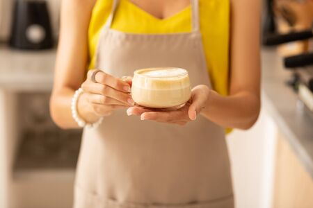 Cup of cappuccino. Close up of female barista wearing brown apron holding cup of cappuccino 写真素材