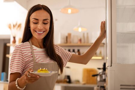 Plate with cake. Pleasant waitress of cafeteria smiling while holding plate with little cake