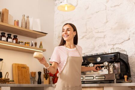 Barista giving coffee. Pleasant barista wearing apron smiling while giving coffee to client