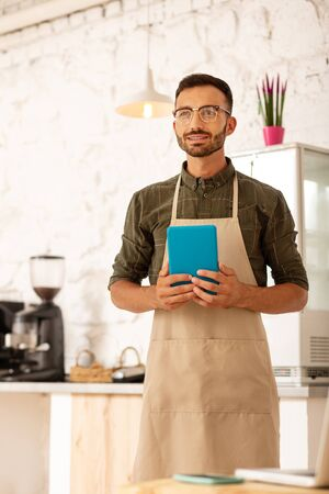 Businessman in apron. Businessman owning coffee shop wearing apron while standing near coffee machine 写真素材