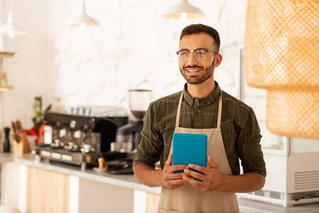 Bearded businessman. Dark-haired bearded businessman owning coffee shop holding little blue tablet