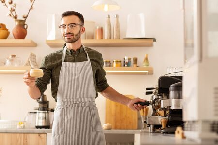 Businessman making coffee. Businessman wearing striped apron while making coffee in his own cafeteria 写真素材