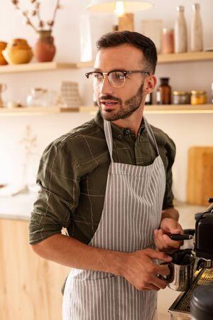 Near coffee machine. Bearded handsome professional barista wearing glasses standing near coffee machine 写真素材