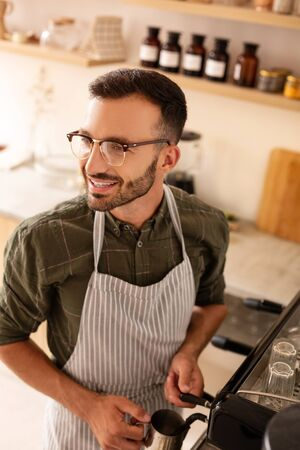 Man making coffee. Handsome dark-haired bearded man smiling while making coffee for customer Stok Fotoğraf