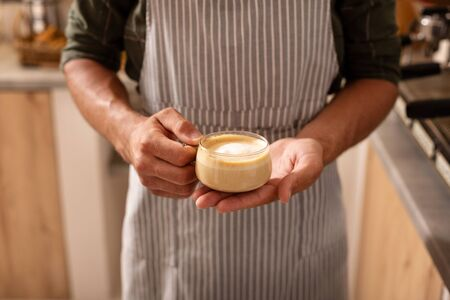 Cup of cappuccino. Close up of professional barista wearing striped apron holding cup of cappuccino 写真素材