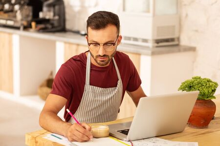 Businessman making notes. Bearded businessman owning cafeteria working on laptop and making notes