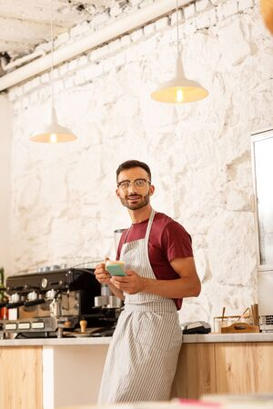 Modern interior. Successful young entrepreneur standing in his own coffeehouse with modern interior Stok Fotoğraf