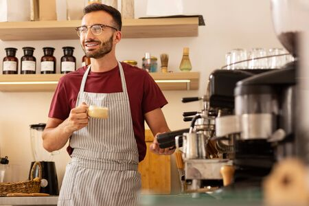 Smiling barista. Cheerful smiling handsome barista standing near coffee machine with cup of coffee Stok Fotoğraf