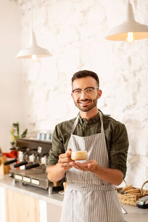 Cup of cappuccino. Handsome bearded entrepreneur owning coffee shop holding cup of cappuccino