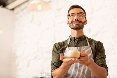 Cup of coffee. Smiling successful businessman owning cafe holding cup of coffee with milk Stok Fotoğraf