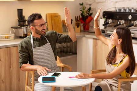 Giving high five. Couple giving high five while feeling happy after opening coffee shop
