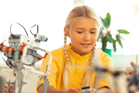 Future scientist. Smiling schoolgirl sitting at her desk during science lesson building a construction set model. Stock Photo