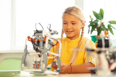 Modern school. Excited schoolgirl with long plaits sitting at her desk and building a robot of construction set at science lesson.