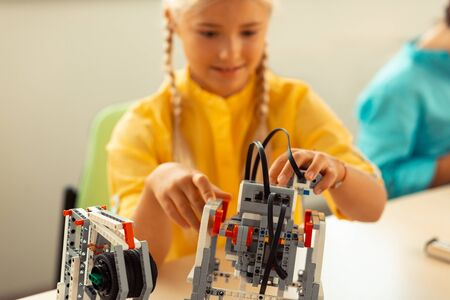 Thinking and creating. Enthusiastic smiling girl building a construction set robot at her school science lesson. Stock Photo