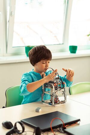 Future engineer. Concentrated elementary school pupil sitting at the desk building his new school project at the lesson. Stock Photo
