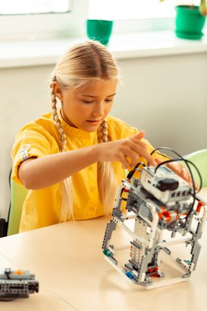 Technical school. Concentrated girl sitting at her science lesson making and turning on robot using construction set.