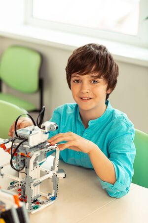 Building models. Cheerful boy sitting at his desk with construction set during his engineering lesson at school.