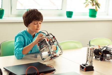 Correcting mistakes. Concentrated schoolboy sitting at the desk in the classroom and looking for mistakes in his robot model made of construction set. Stock Photo
