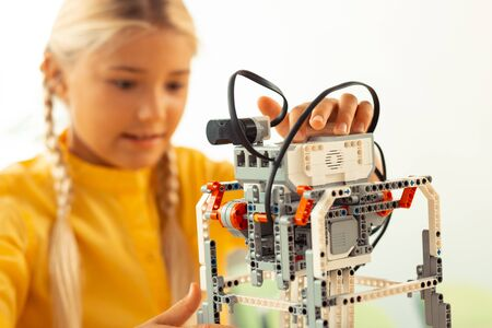 Feeling like a scientist. Concentrated schoolgirl working with a robote made out of construction set at the lesson.
