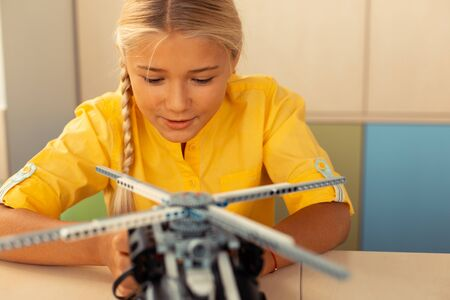 Trying new. Enthusiastic schoolgirl sitting at the desk in the classroom beginning launching a helicopter model.