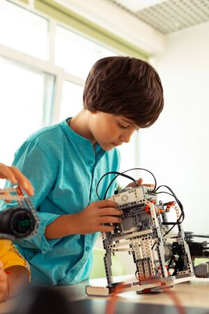 Robotic hobby. Concentrated elementary schoolboy standing in the classrom near his desk checking his complicated science project made of construction set.