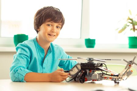 Building of models. Happy smiling boy sitting with a helicopter model made of construction set attending his school science class. Stock Photo