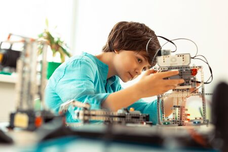 Setting right. Enthusiastic elementary school pupil fixing the robot made of cconstruction set at science lesson. Stock Photo