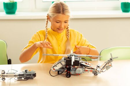 Trying in work. Concentrated enthusiastic schoolgirl raising her hand above helicopter model she made turning it on during her lesson. Stock Photo