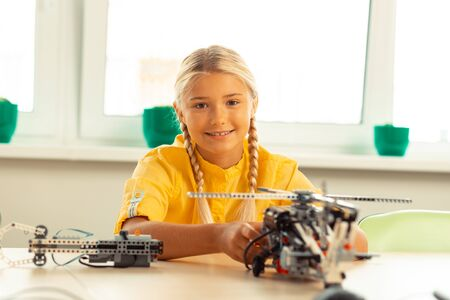 Ready to learn. Cheerful blonde girl sitting at the desk with a helicopter model on it during her technology lesson. Stock Photo