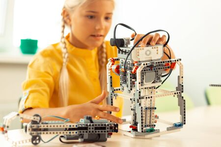 Glad to learn. Enthusiastic girl sitting at the school desk and building a robot using construction set during her science lesson.