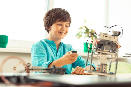 Little test engineer. Cheerful boy sitting in the classroom being happy trying his robot model at the science lesson.