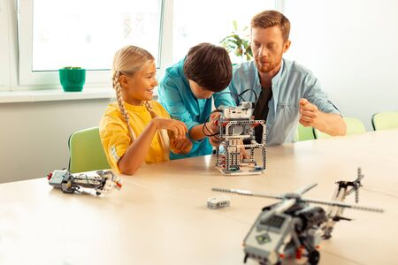 Lending a helping hand. Enthusiastic boy standing between his teacher and classmate sitting at the school desk helping a girl building her robot. Stok Fotoğraf