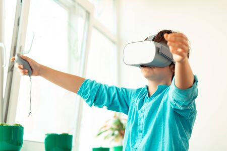 Playing games. Elementary schoolboy wearing big VR glasses raising his hands to the sides being wrapped up in virtual reality.