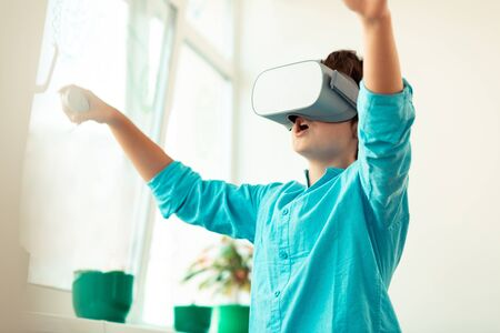 Technological innovetions. Excited schoolboy wearing VR glasses raising hands playing virtual games in the classroom.