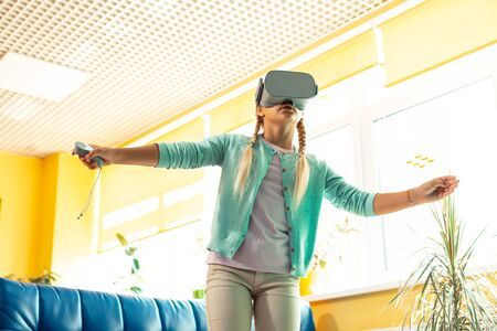 Fascinating feelings. Enthusiastic schoolgirl holding her arms sideward wearing VR glasses being wrapped up in virtual reality.