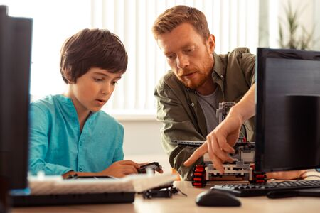 Helping to improve. Serious teacher showing a concentrated pupil building a robot out of construction set his mistakes in the project. Фото со стока