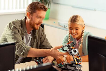 Good job. Attentive teacher evaluating the robot made out of construction set by the schoolgirl sitting next to him. Фото со стока