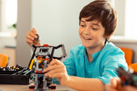 Almost ready. Happy boy finishing his work on the complicated robot made with construction set during science lesson.