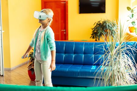 Entering different reality. Amused girl wearing big VR glasses standing in the middle of the hall being in virtual world during her school breaktime.